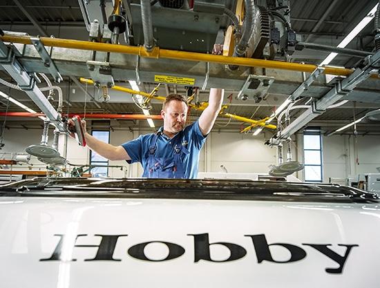 Technik servisuje obytné auto Hobby na střeše
